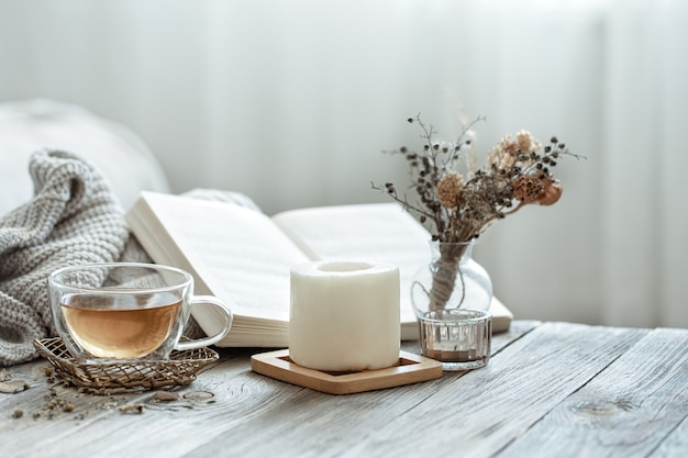 A cozy composition with a cup of tea, a book and decor details in the interior of the room on a blurred background.
