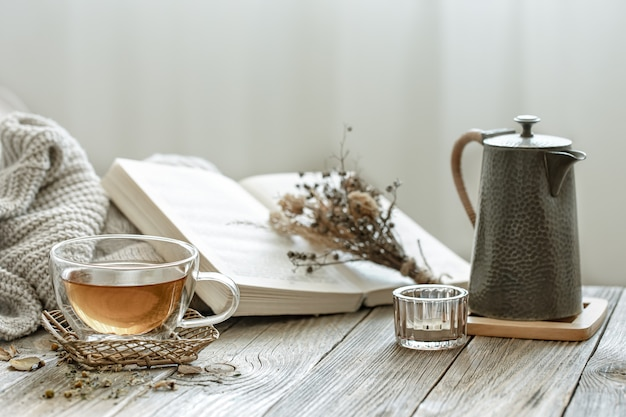 Cozy composition with a cup of tea and a book in the interior of the room on a blurred background.