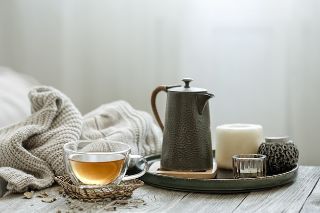A cozy composition with a cup of tea, a candle in the interior of the room on a blurred background.