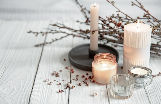Cozy composition with flaming candles and young tree branches on a wooden surface in the scandinavian style.