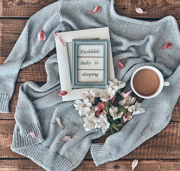 Уютная концепция. снимок свитера, цветов, чашки кофе и фоторамки на деревянном столе под высоким углом