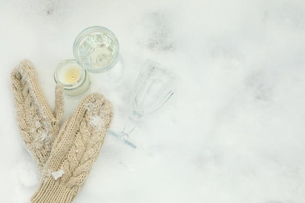 冬の屋外のメガネ、キャンドル、ミトンと居心地の良いコンセプト