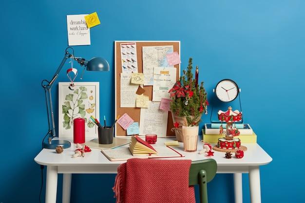 Accogliente spazio di coworking con blocco note, abete decorato, bevanda fresca a base di dolciumi giornalieri, candela rossa incombusta, sedia con plaid, note scritte a mano.
