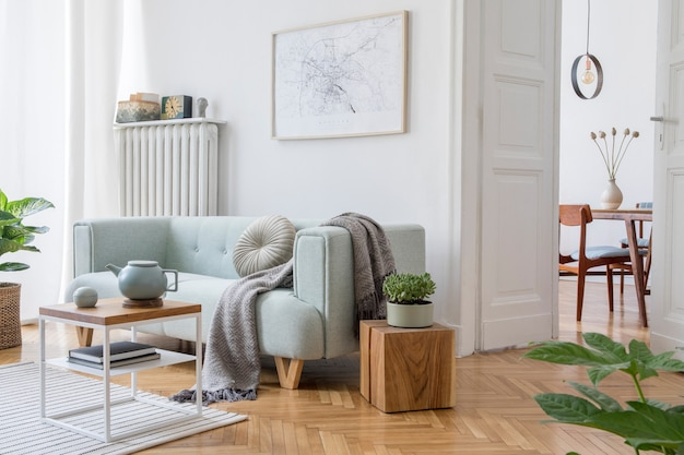 Cozy and creative composition of stylish living room interior design with mock up poster frame, green sofa, wooden furniture, plants and accessories. white walls, parquet floor. template.