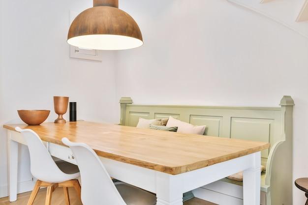 코너에 흰색과 나무 테이블이 있고 펜던트 램프 아래에 녹색 클래식 벤치가있는 아늑한 식사 공간