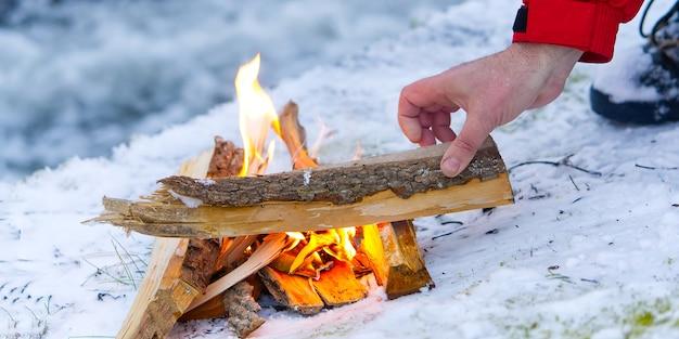 겨울에 강둑에 아늑한 불. 겨울철에 작은 따뜻한 모닥불. 겨울에는 눈에 강 캠프 파이어