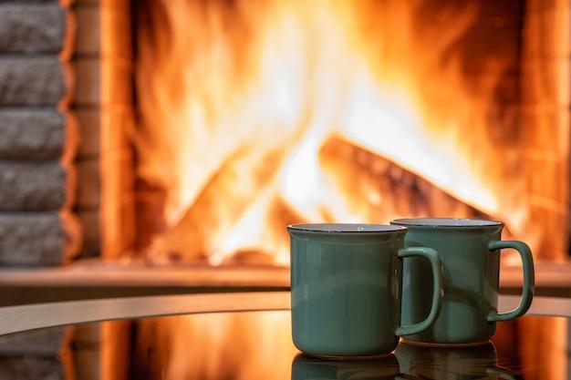 Уютный камин и чайные кружки, отражение огня на стеклянном столе.