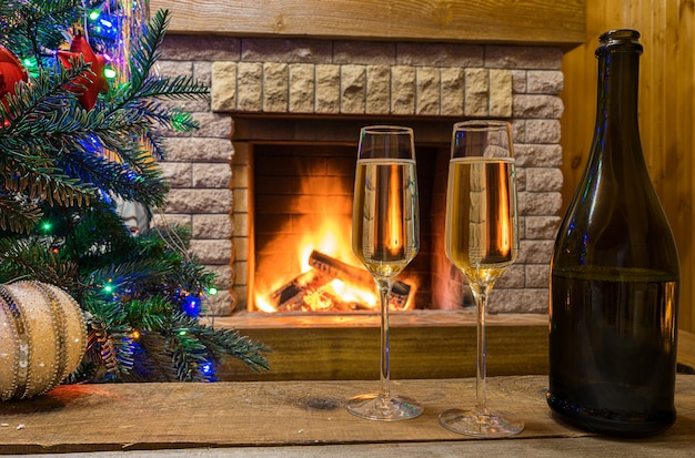 Cozy fireplace. champagne wine before christmas tree decorated toys and christmas lights in country cottage.