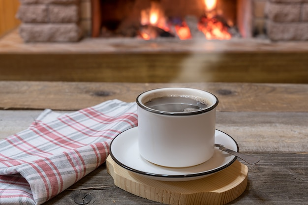 Cozy fireplace and a cup of tea, in country house, winter vacation.