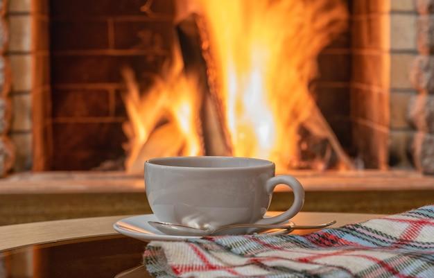 Уютная сцена у камина, чай льется в белую чашку, печенье на столе.