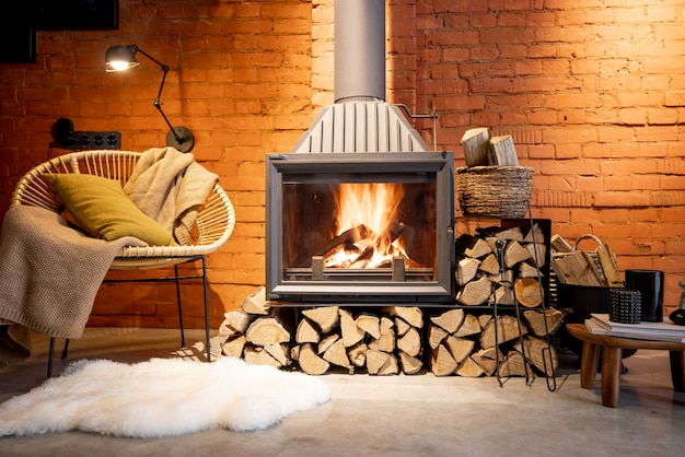 Уютный камин на дровах в стиле лофт, домашний интерьер на фоне кирпичной стены, горящий огонь в камине, домашний уют зимой