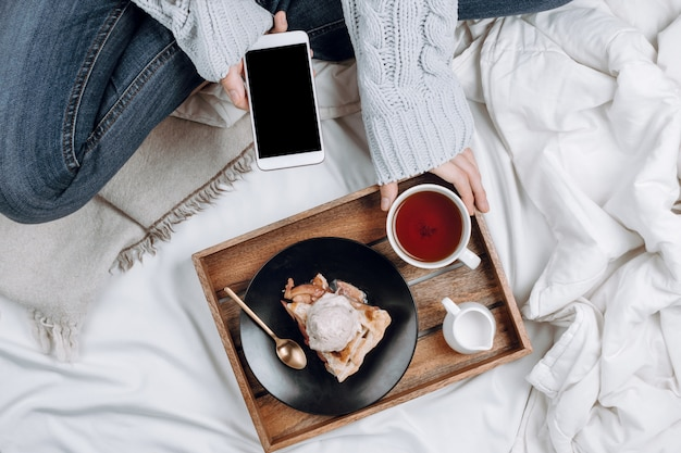 Cozy flatlay of bed with wooden tray with vegan apple pie, ice cream and black tea and woman in jeans and grey sweater holding smartphone with black copyspace on white sheets and blankets