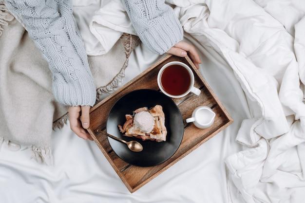 Уютная плоская кровать с деревянным подносом с пирогом, мороженым и черным чаем и женскими руками в сером свитере с чашкой