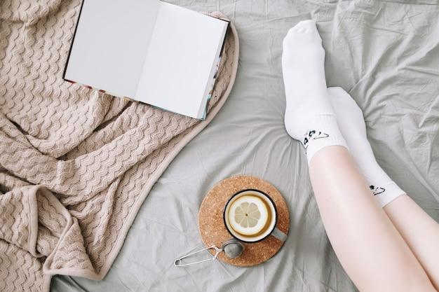 Уютная квартира женских ног в белых чулках в постели с вязанным свитером и книгой и чашкой лемо