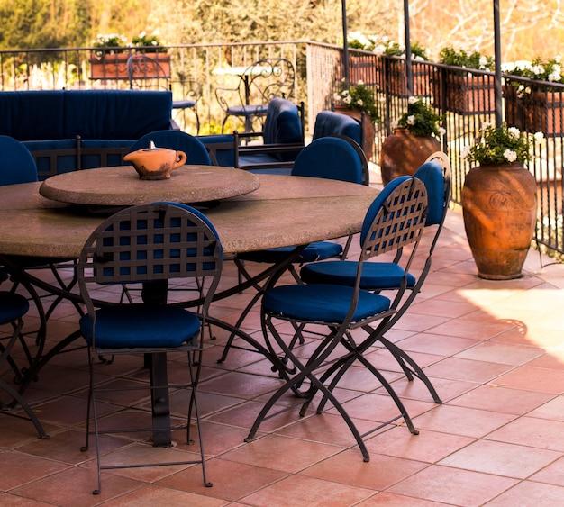 庭を見下ろすバルコニーまたはテラスにある居心地の良い鍛造家具。休憩所