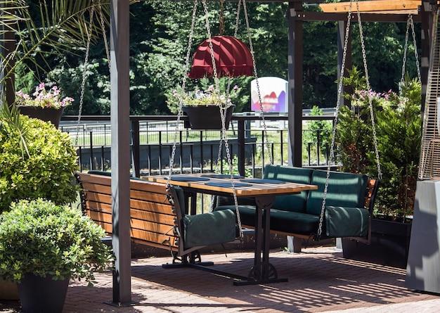 Уютные зеленые качели на цепях вместо стульев в открытом ресторане курортного городка