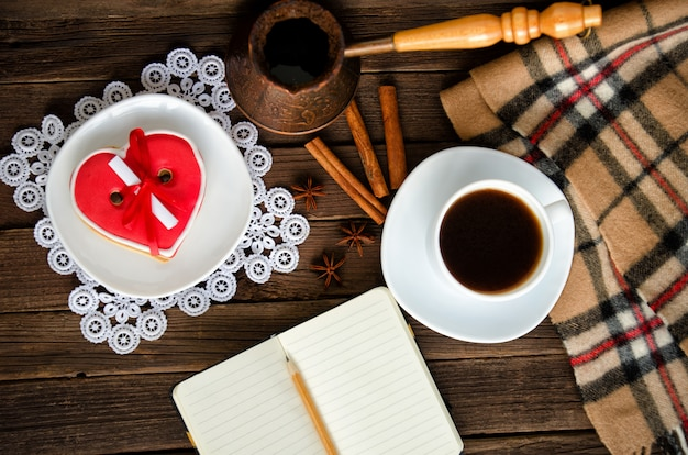Cozy holiday. mug coffee pots, heartshaped gingerbread, notepad and pencil, plaid and spices. top view