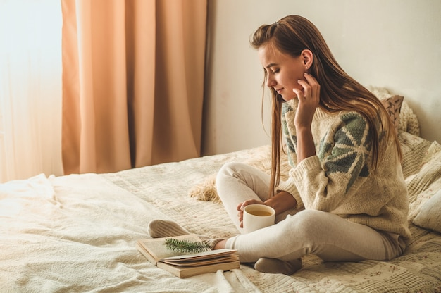 Уютный дом. красивая женщина читает книгу на кровати. доброе утро с чаем и книгой. довольно молодая женщина расслабляющий. концепция чтения