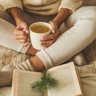 Cozy home. beautiful woman is reading a book on the bed. good morning with tea and book. pretty young woman relaxing. the concept of reading