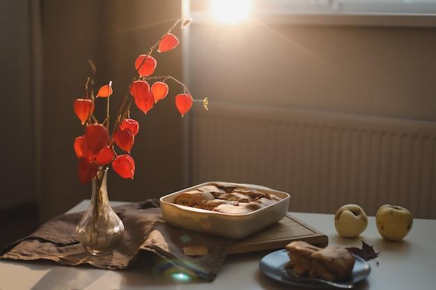 Уютный домашний завтрак с яблочным пирогом, букет красных цветов на столе в солнечной комнате
