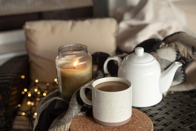 Уютная домашняя композиция с чашкой кофейного напитка, чайником и горящей свечой. концепция домашнего уюта.