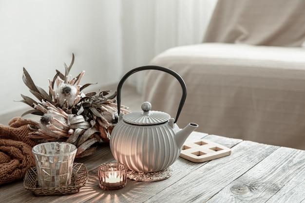 Уютная домашняя композиция с чайником и деталями декора в интерьере комнаты.