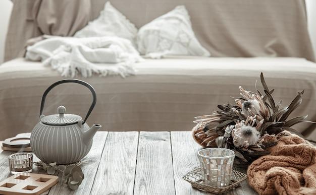 Уютная домашняя композиция с чайником и деталями декора в интерьере комнаты