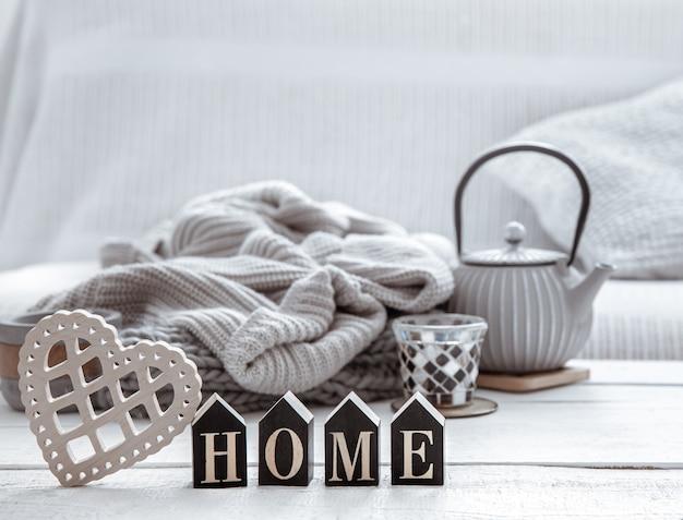 ティーポット、ニットアイテム、スカンジナビア風の装飾が施された居心地の良い家の構図。家の快適さとモダンなスタイルのコンセプト。