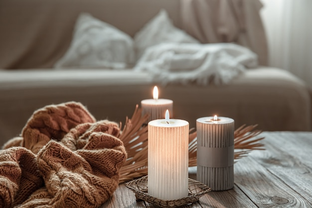 Cozy home composition with burning candles on a wooden table with a knitted element