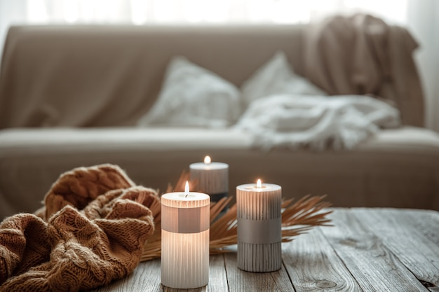 Cozy home composition with burning candles on a wooden table with a knitted element.