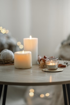 Cozy home composition with candles on blurred bokeh background.