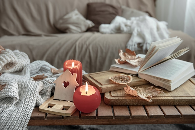 A cozy home composition with candles, a book, knitted sweaters and leaves in the interior of the room.
