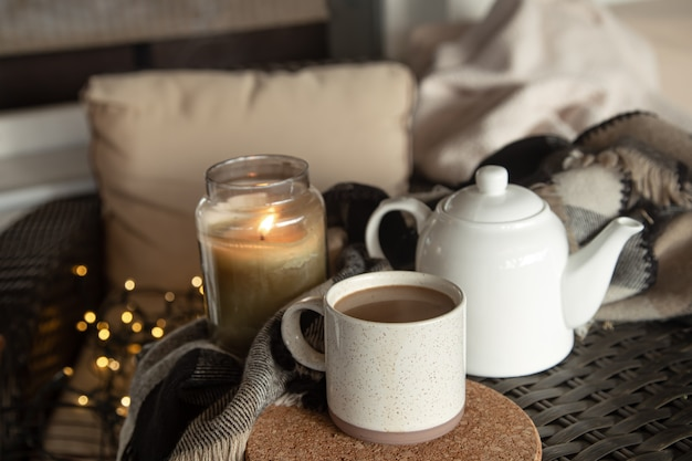 Cozy home composition with a cup of coffee drink, a kettle and a burning candle. home comfort concept.
