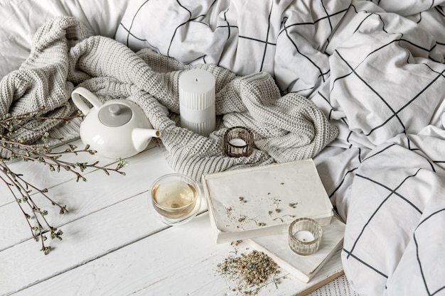 Accogliente composizione domestica con una tazza di tisana e libri su una superficie di legno.