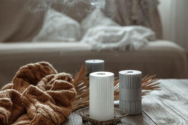니트 요소가 있는 나무 테이블에 촛불이 꺼진 아늑한 집 구성.