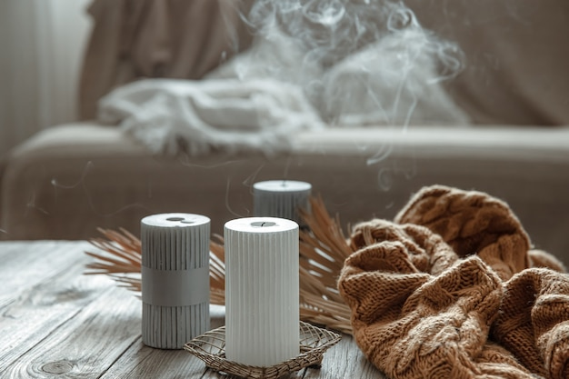 Cozy home composition with extinguished candles on a wooden table with a knitted element.