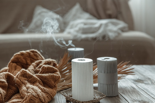 Cozy home composition with extinguished candles on a wooden table with a knitted element