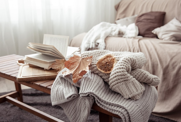 A cozy home composition with a knitted sweater, a book and leaves in the interior of the room.