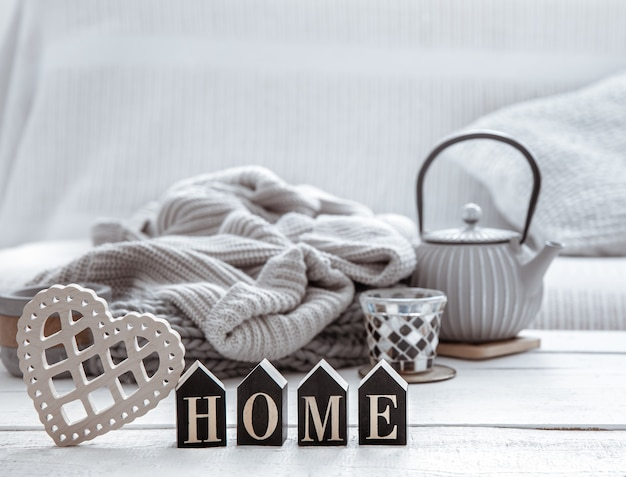 Accogliente composizione per la casa con teiera, articoli in maglia e dettagli di arredo scandinavo. il concetto di comfort domestico e stile moderno.