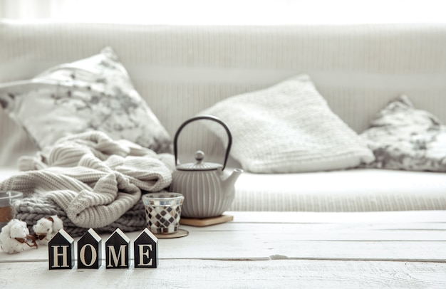 Accogliente composizione per la casa con teiera, articoli in maglia e dettagli di arredo scandinavo