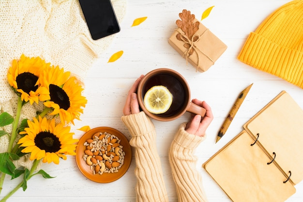 Cozy home concept autumn flat lay with female hands holding cup of tea