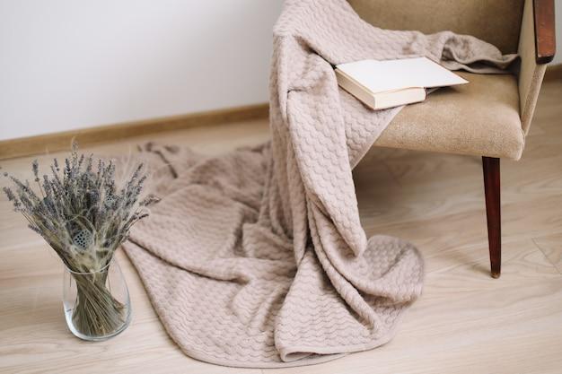 Уютный домашний декор. кресло с пледом и книгой, ваза с букетом лаванды. современный дизайн интерьера дома.