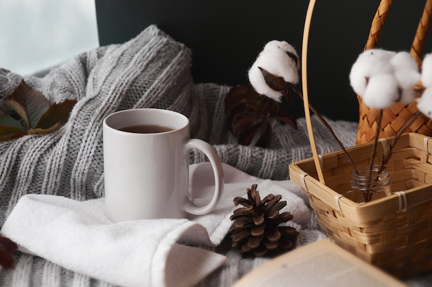Cozy home decor with a warm atmosphere. white mug with hot tea and knitted clothes