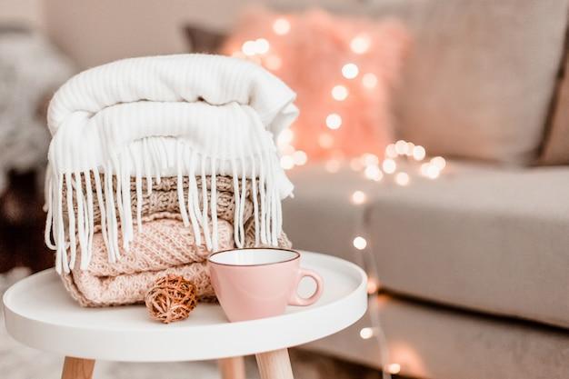 インテリアに居心地の良い家の装飾、リビングルームに編み物とマグカップ
