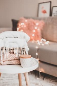 Уютные украшения для дома в интерьере с вязанием и кружкой в гостиной