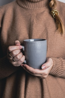 Cozy home female hands holding hot cup of tea