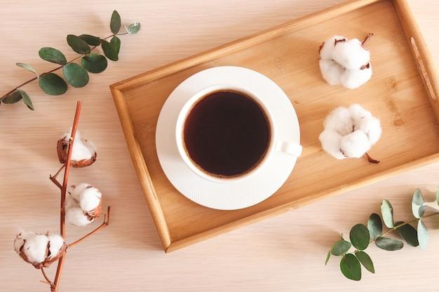 Уютная домашняя плоская чашка кофе с листьями эвкалипта и цветами хлопка