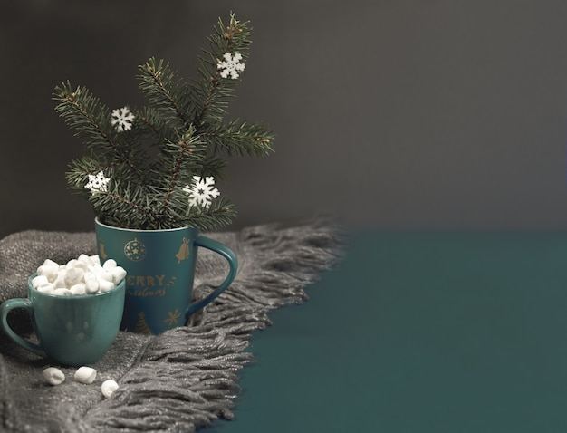 Cozy home hugge christmas or new year background with xmas mug with fir branches, snowflakes, cup of coffee or cocoa with marshmallows on grey knitted plaid on dark. selective focus. copy space.