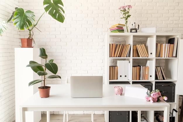 Уютный домашний интерьер. стильное уютное рабочее место с ноутбуком, книжными полками и растениями
