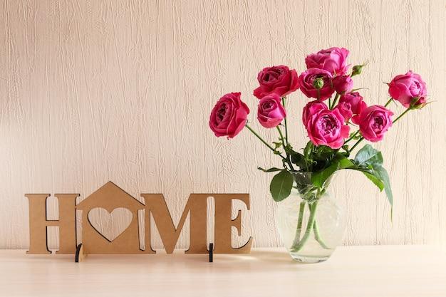 Уютный домашний интерьер деревянный декор с надписью home и ваза с розовыми цветами copy space